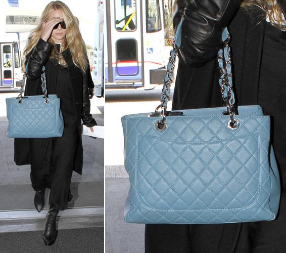 Tentando esconder o rosto dos paparazzi ao desembarcar em um aeroporto, Ashley Olsen deixa à mostra sua Chanel azul bebê matelassada e com alça de corrente larga