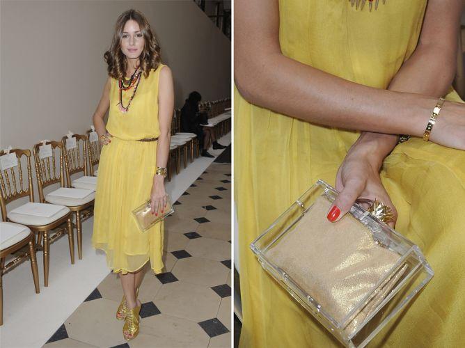A clutch Charlotte Olympia usada por Olivia Palermo lembra um frasco de perfume. Ela é quadrada, de acrílico transparente, com um fecho dourado e um forro de tecido, também dourado, para não revelar o que a socialite carrega