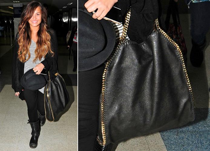 Demi Lovato usa bolsa grande Stella McCartney do modelo Falabella que é de couro falso com correntes de metal nas laterais que também formam as alças da peça