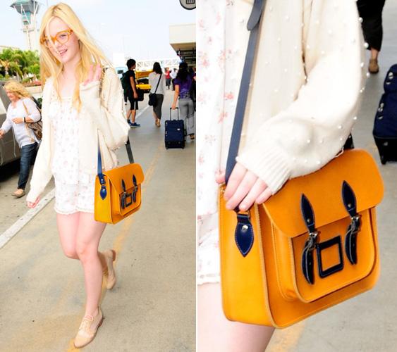 A jovem atriz Elle Fanning mostra que tem talento fashionista ao escolher uma bolsa-carteiro mostarda com alça e fivelas em azul marinho