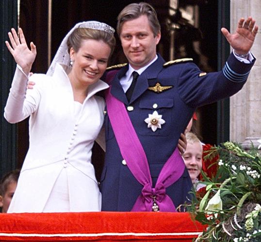Princesa Mathilde, da Bélgica, acena ao lado do marido, príncipe Philippe durante seu casamento em 1999. A noiva usou vestido comportado, acinturado com mangas compridas e gola alta do estilista belga Edouard Vermeulen