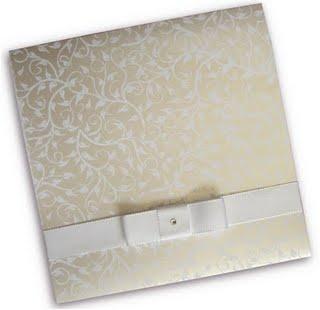 Modelo quadrado em papel branco liso com impressão de folhagem vazada em silk screen pérola com amarração em laço estilo Chanel com fita de cetim branca; R$ 499 (100 unidades), na Art Invitte