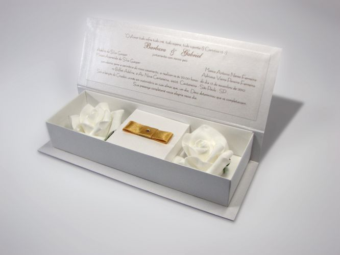 Convite feito em papel da Color Plus Metálico cor Aspen. O envelope consiste em uma caixa revestida com papel Opalina Liso Branco, acompanha duas rosas brancas artificiais, hot stamp dourado das iniciais na tampa com strass cristal e lacre de fita de cetim com laço Chanel duplo e strass; R$ 2.522 (100 unidades), de Andréa Nocera