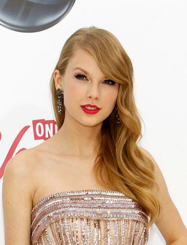 Para um visual bem feminino e atemporal, nada como os cabelos penteados para o lado em ondas macias e maquiagem com batom vermelho e cílios postiços volumosos, como usa Taylor Swift na foto
