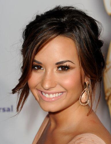 Se você está sempre bronzeada como Demi Lovato, uma boa pedida para festas é realçar o tom da pele com produtos em tons de dourado e acobreados. Assim você consegue copiar essa maquiagem com sombra acobreada formando um