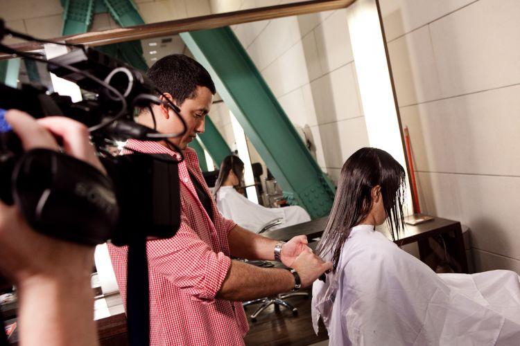 O cabeleireiro finaliza o corte, diminuindo um pouco mais o comprimento e formando camadas para dar movimento aos cabelos de Solange Lima, a primeira participante do programa