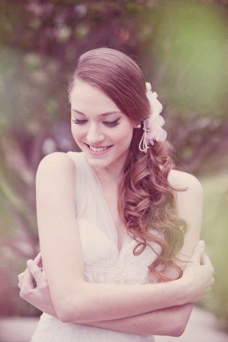 O romantismo é uma tendência em alta na beleza das noivas, como mostra esse penteado meio preso lateral com arranjo em tom rosa claro