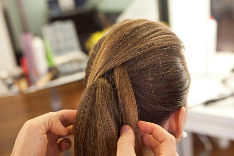 Coque estilizado e volume no topo da cabeçaSepare os cabelos da frente em duas mechas e cruze-as, atrás, sobre o elástico. Se a franja não for longa o suficiente para envolver o elástico pode deixá-la solta lisa de lado