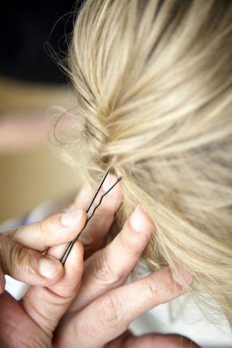 Flor com cabelo semi-preso e topete desmanchadoSepare uma mecha de cada lado, enrole no sentido das laterais para dentro e prenda com um grampo centralizado atrás da cabeça