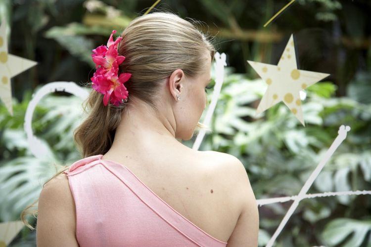 Flor com cabelo solto e de ladoFinalize e esconda os grampos com uma presilha grande (ou duas menores), do tipo bico de pato. Esta é enfeitada com orquídeas. Na frente os cabelos ficam soltos, de um lado só, bem natural