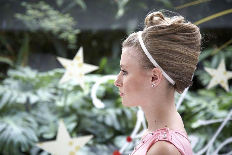 Flor na tiara com coque bananaA lateral do penteado cria um volume alto na cabeça
