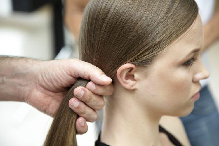 Com elástico em gomosEscove bem os cabelos para o lado oposto da risca, deixando-os bem polidos