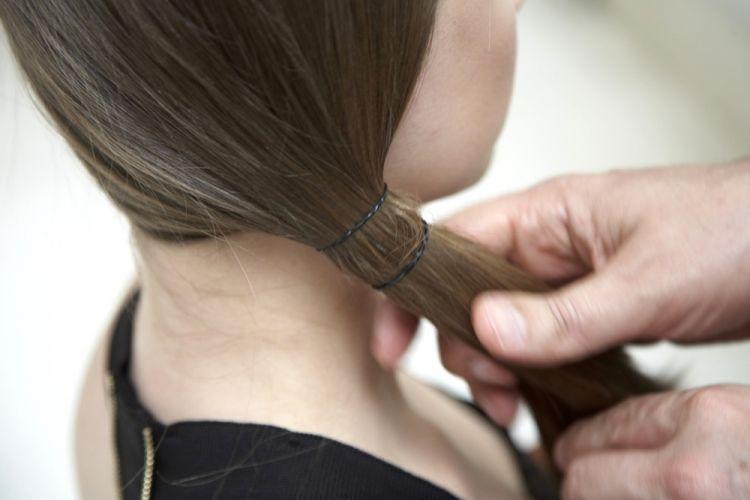 Com elástico em gomosPosicione os cabelos para cobrirem a orelha e faça um rabo de cavalo baixo na lateral escovando bem os fios. Prenda com um elástico fininho de silicone e dois dedos abaixo coloque outro elástico