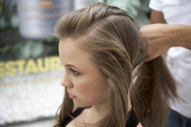 Alto com trancinhas lateraisSepare uma porção de cabelo em cada uma das laterais da cabeça, deixando uma mecha central entre elas. Prenda essa mecha central da frente com o restante do cabelo atrás