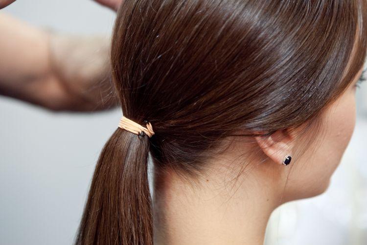 Prenda o cabelo num rabo baixo, usando um elástico