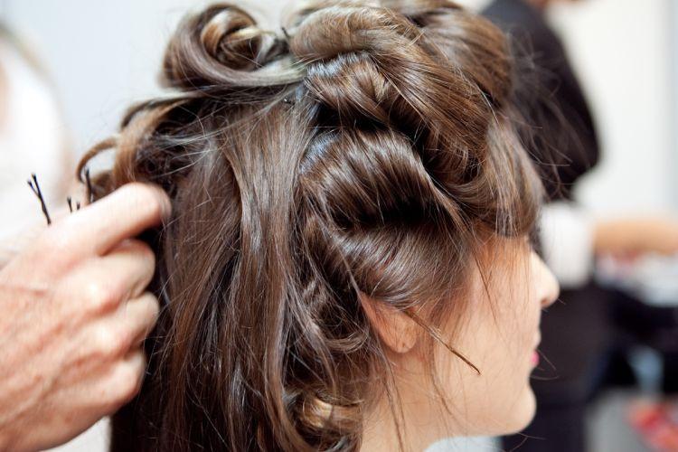 Para o segundo penteado, usando o véu curto, comece fazendo uma escova e prendendo todo o cabelo em bobes médios por meia hora