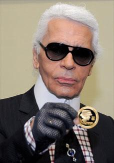 O estilista Karl Lagerfeld mostra a moeda de 5 euros criada em homenagem a Coco Chanel