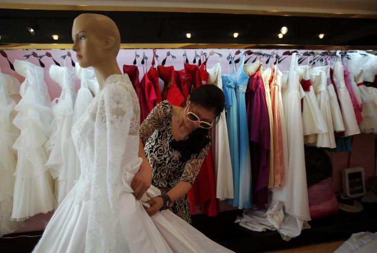 A estilista chinesa Yang Lifei faz ajustes no vestido de noiva cópia do modelo usado por Kate Middleton em seu casamento com o príncipe William (05/05/2011)