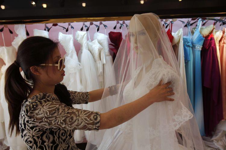 A estilista chinesa Yang Lifei ajusta o véu em cópia do vestido de noiva de Kate Middleton, usado em seu casamento com o príncipe William. A peça original foi criada por Sarah Burton, da Alexander McQueen (05/05/2011)