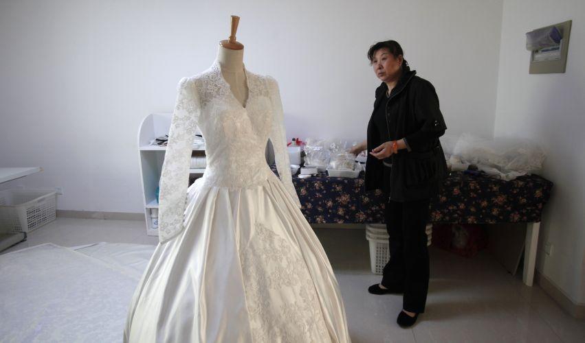 Mulher observa cópia do vestido de noiva de Kate Middleton em ateliê da estilista Yang Lifei, em Suzhou, na China