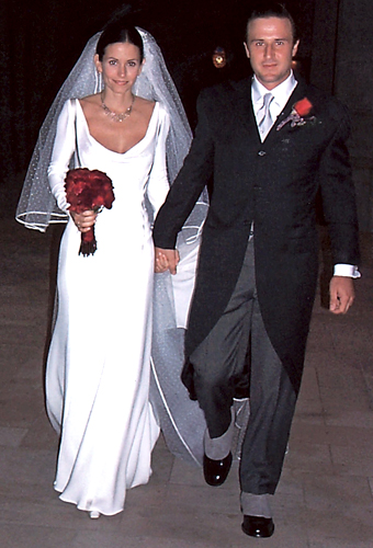 Courtney Cox, de vestido Valentino com mangas compridas e saia contida, em seu casamento com o ator David Arquette, em 1999