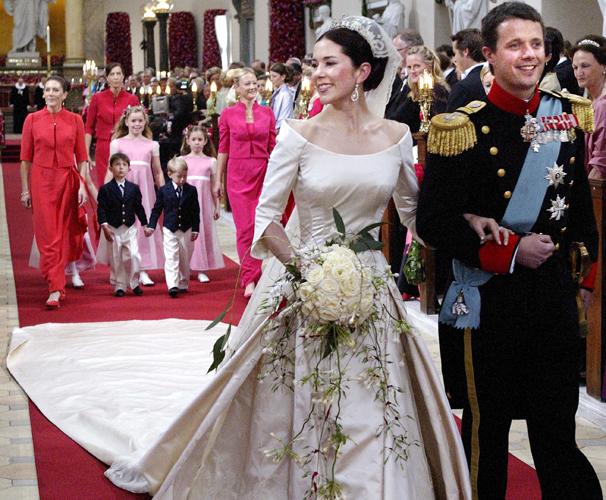 Princesa Mary, da Dinamarca, usa vestido comportado com manga 3/4 criado pelo estilista dinamarquês Uffe Frank em seu casamento com o príncipe Frederick, em 2004
