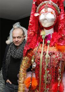 O estilista Christian Lacroix posa ao lado de uma de suas criações, que integram a exposição